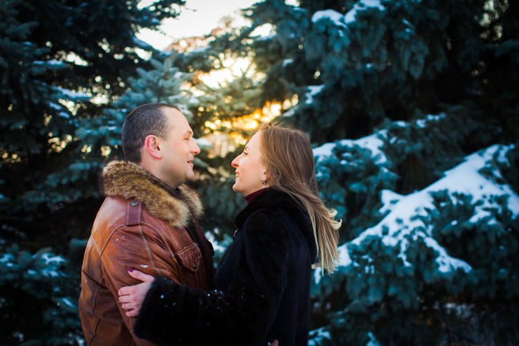 Side view of couple standing against snow covered trees during winter