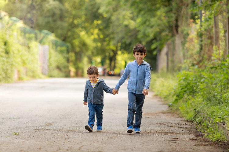 Brothers walking on road