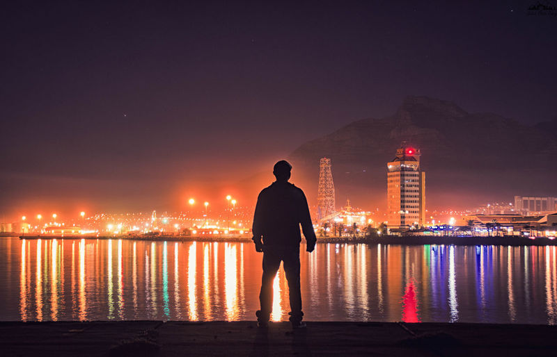 Silhouette man looking at view while standing by sea in illuminated city at night