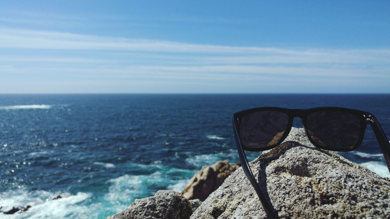 Close-Up Of Sunglasses On Rock By Sea Against Sky