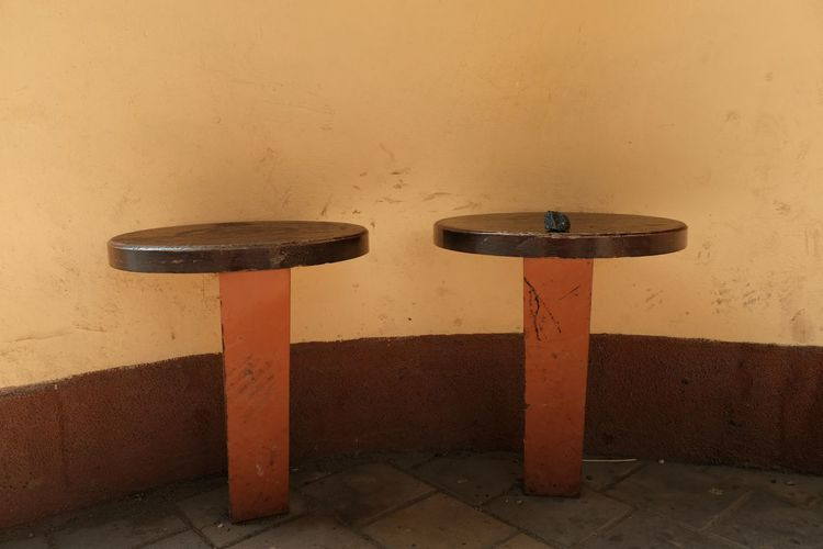 Empty seats on footpath against wall