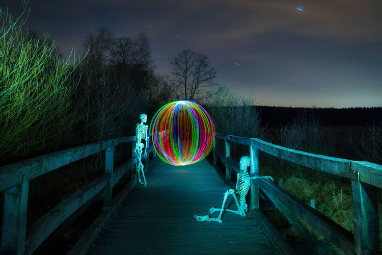 Light painting on railing against sky at night
