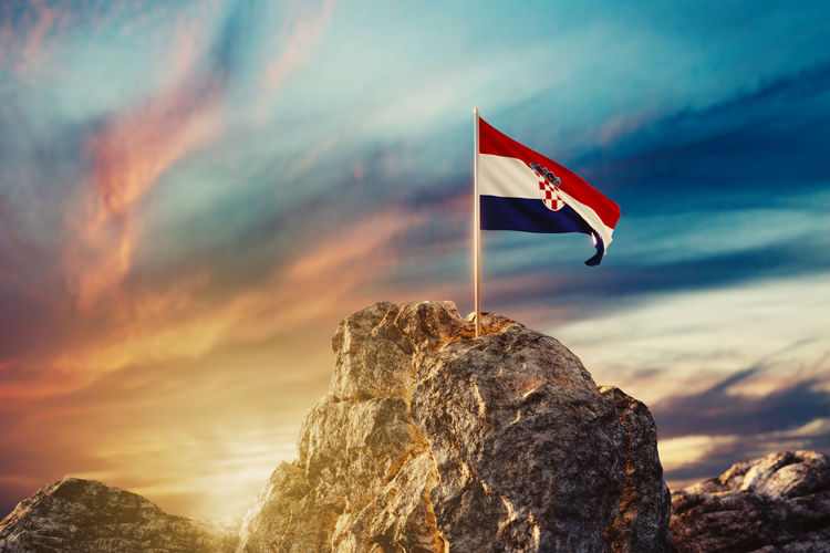Waving Croatian flag on rocky landscape in the evening sunlight Croatia Waving Waving Flag Beauty In Nature Croatian Evening Flag Independence Mountain Mountain Peak Mountain Range Outdoors Patriotism Peak Rock Rock - Object Rock Formation Sky Sunset Tranquility Wind