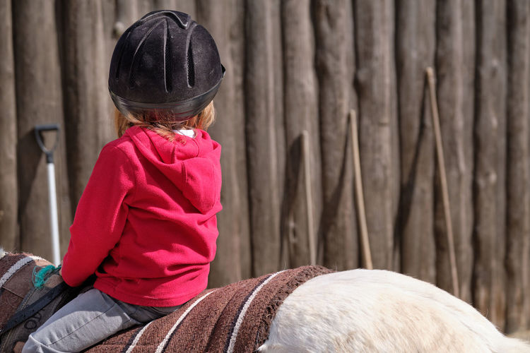 Rear view of girl riding horse