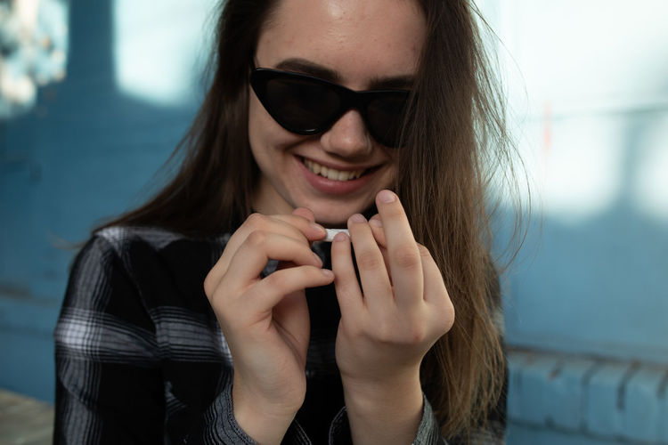 Smiling young woman wearing sunglasses while holding paper