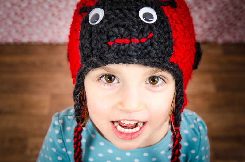 High angle portrait of smiling girl wearing knit hat standing on hardwood floor at home