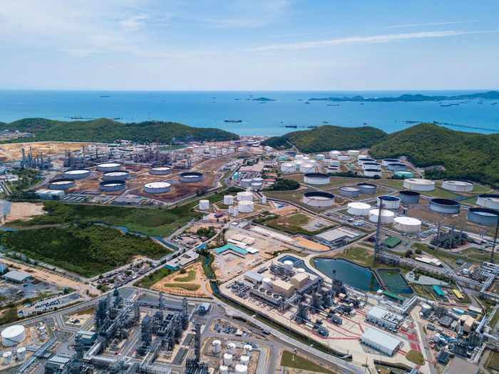 Aerial view of petrochemical oil refinery and sea in industrial engineering concept in Laem Chabang, Chonburi province, Thailand. Oil and gas tanks industry. Modern factory. Top view. Horizon Over Water Land Cloud - Sky Scenics - Nature Outdoors No People Aerial View Building Day Residential District Nature Sky High Angle View Built Structure Water Building Exterior Steam Tube Background Chemistry Pollution Chemical Port Petrol Architecture Urban Smoke Construction Business Storage Tank Pattern Transportation Hill Cityscape Town Tourism Travel City Station Petroleum Pipe Fuel Engineering Industrial Power Environment Equipment Technology Plant Chonburi Production Industry Gasoline Aerial Factory Thailand Top Gas Oil Energy Sea Blue Petrochemical Refinery Buildings