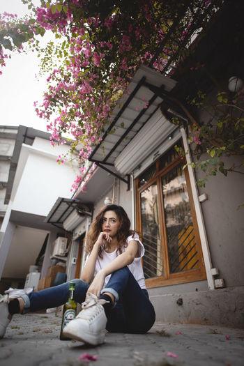 Portrait of woman sitting against built structure