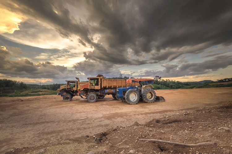 Tractor And Trucks On Field Against Sky During Sunset