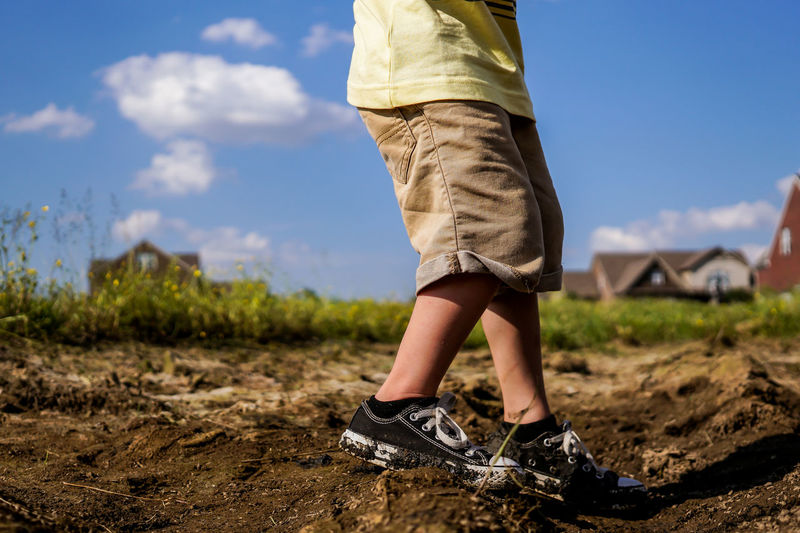 Child Walking Through Mud Wearing Muddy Shoes One Person Low Section Sky Nature Day Real People Outdoors Sunlight Summer Summertime Boy Child Tennis Shoes Muddy Shoes Mud Dirt Dirty Shoes Playing Fun