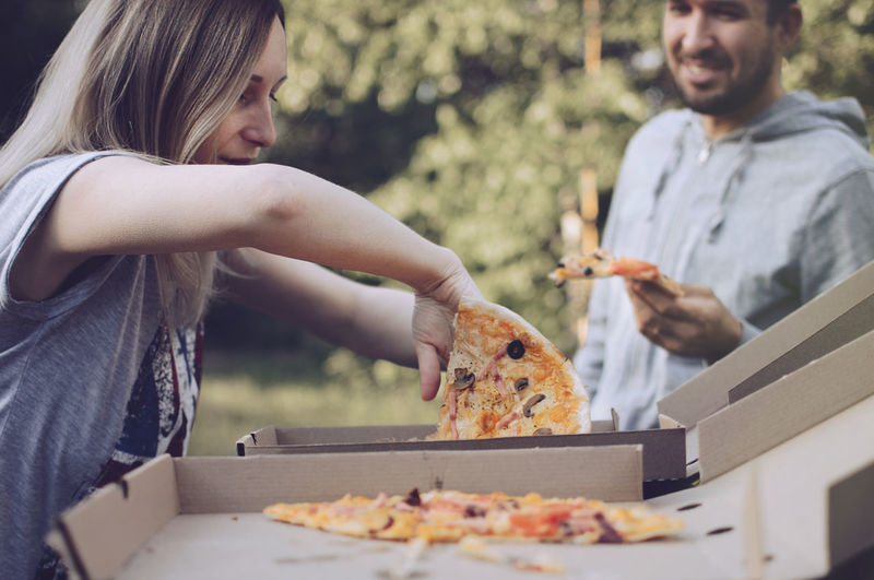 Young woman removing pizza from box