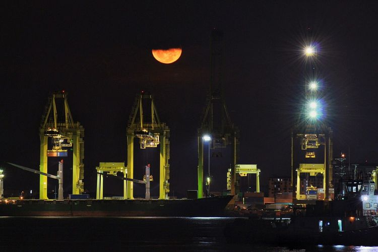 Cranes At Harbor Against Sky During Night