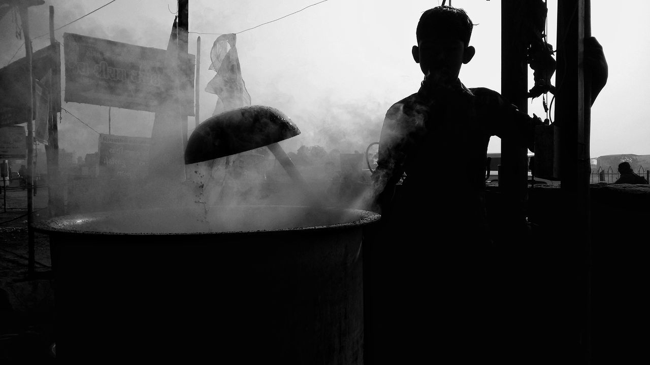 Silhouette man preparing food in container