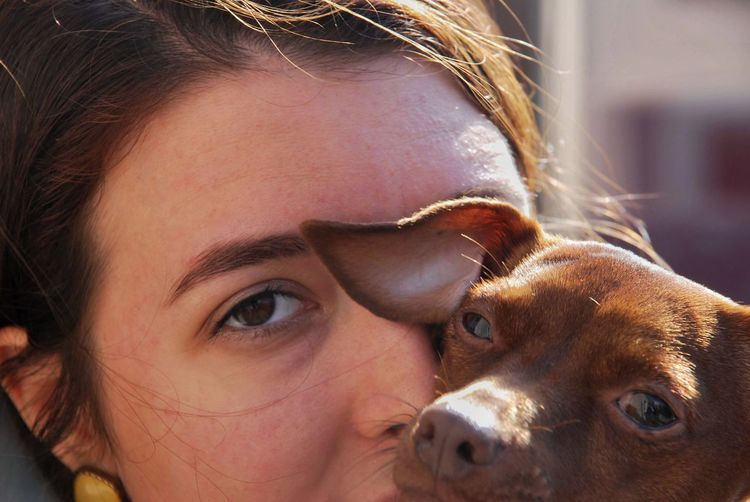 Close-up portrait of young woman with dog outdoors