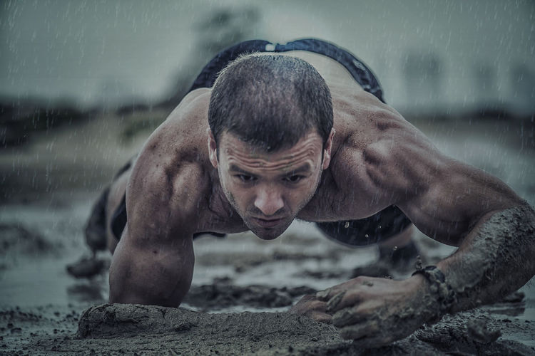 Close-up of athletic man exercising in mud during rainy season