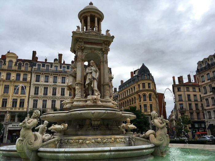 Statue of buildings against cloudy sky