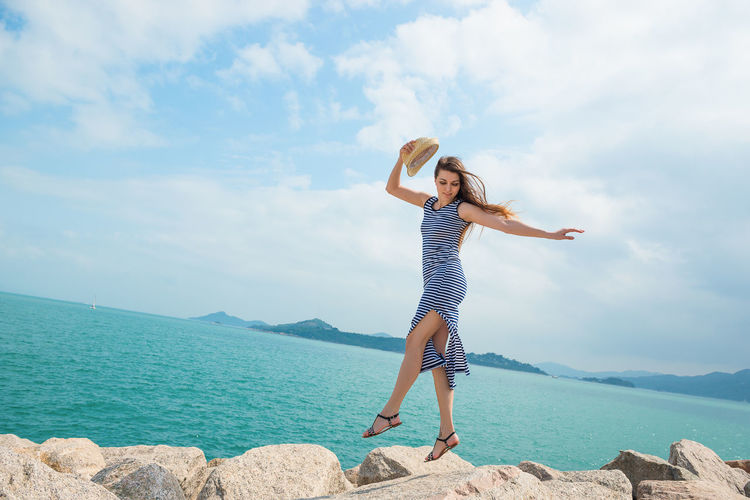 Woman jumping over rocks by sea against sky