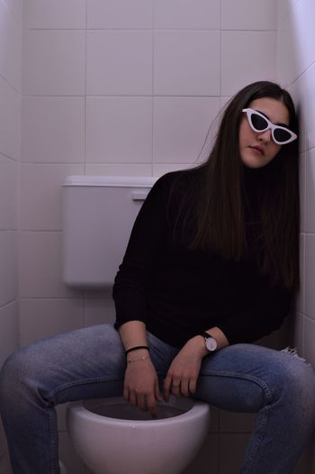 Portrait of young woman in sunglasses sitting on toilet bowl