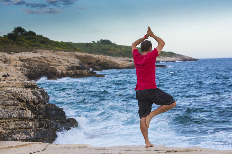 Rear view full length of man practicing tree pose against sea