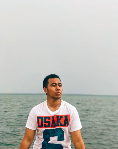 Young man standing in sea against sky