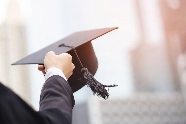 Cropped hand of person holding mortarboard