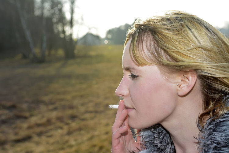 Profile View Of Woman Smoking Cigarette On Field