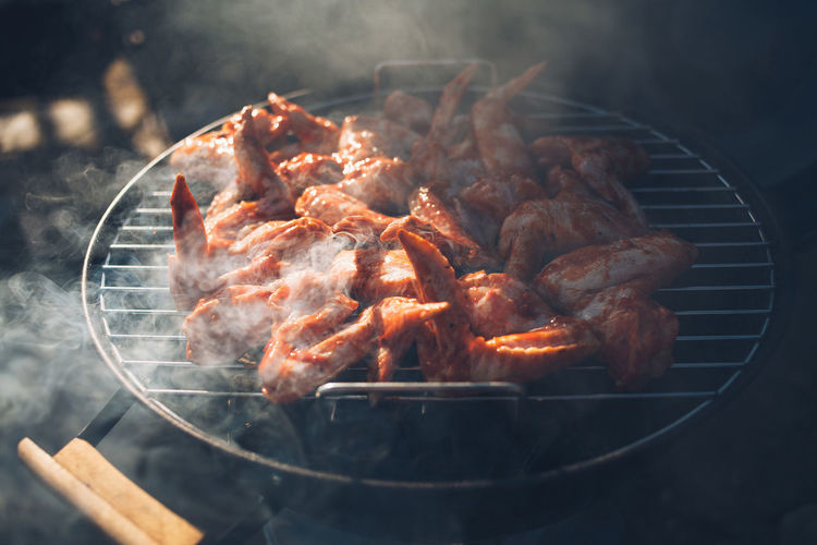 chicken wings lie on a steaming barbecue grill.