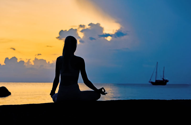 Silhouette of young woman sitting  in meditation on the rock by the sea against sky on sunrise
