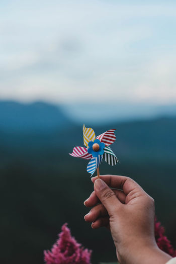 Cropped hand holding pinwheel toy against sky