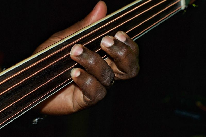 Cropped hand of man playing guitar against black background