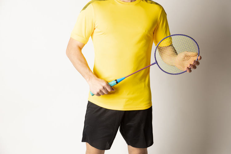 Midsection of man holding yellow while standing against white background