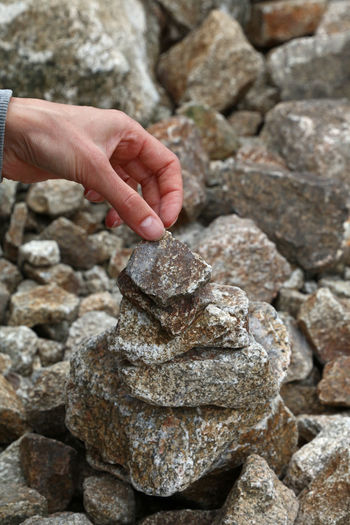 Cropped Hand Of Woman Adjusting Stone Stack
