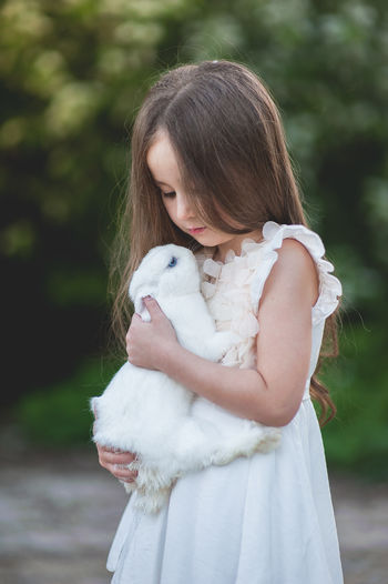 Girl carrying rabbit while standing against trees