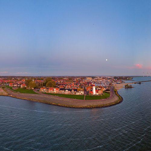 Illuminated city by sea against blue sky urk netherlands