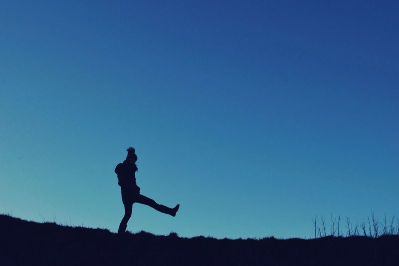 Silhouette Woman Kicking On Field Against Clear Blue Sky