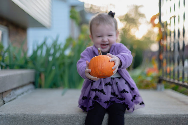 Girl laughing while holding pumpkin on land