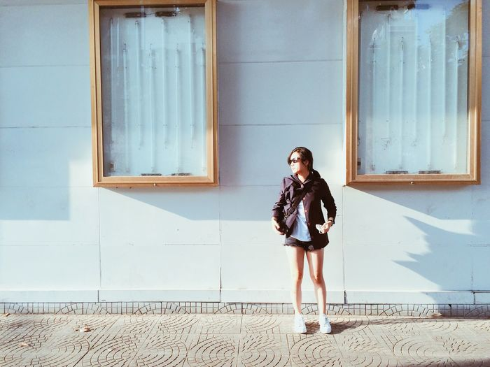 Full length of young woman standing against building on sunny day