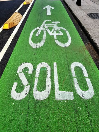 Bicycle lane sign and text on road