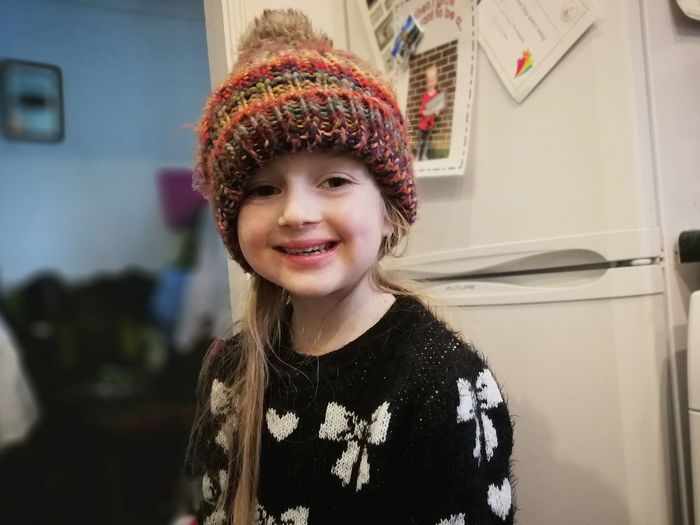 Portrait of smiling cute girl against refrigerator at home