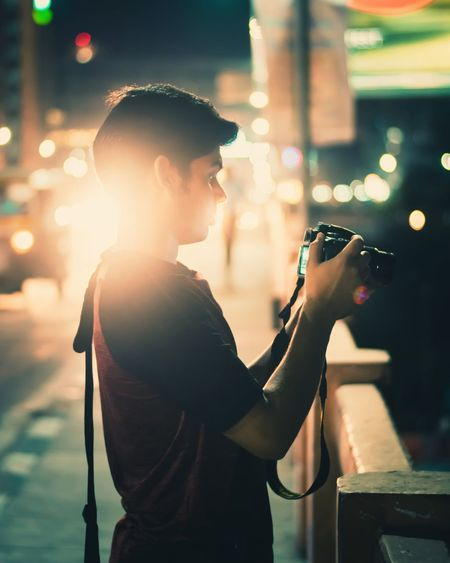 Side view of young man photographing while standing on bridge in city at night