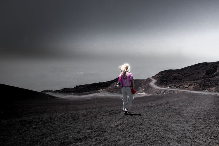 Woman walking on land against sky