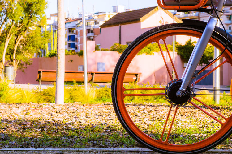 Nature No People Day Outdoors Sunlight Sun Transportation Land Vehicle Bicycle Mode Of Transportation Wheel Focus On Foreground Close-up Stationary Architecture Built Structure Metal Field Building Exterior Plant City Tire Spoke Orange Color