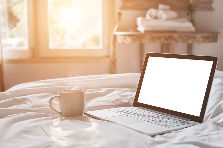 Table and laptop on bed at home
