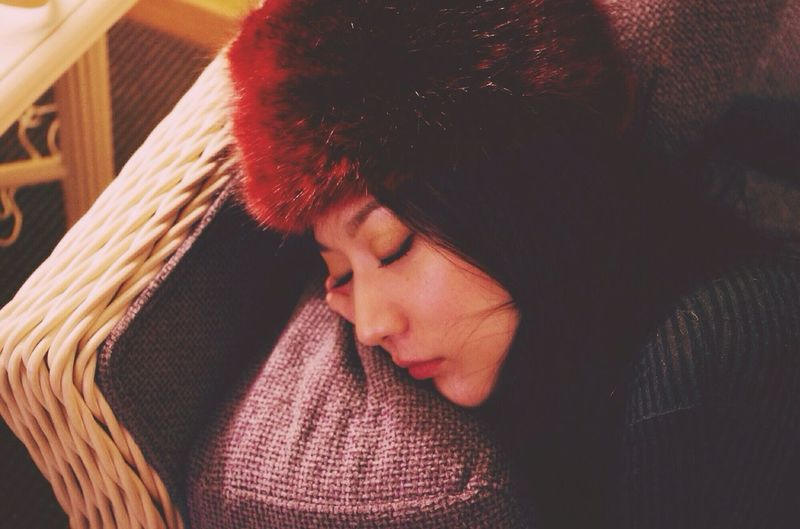 High Angle View Of Young Woman Sleeping On Wicker Furniture In Living Room With Fur Hat