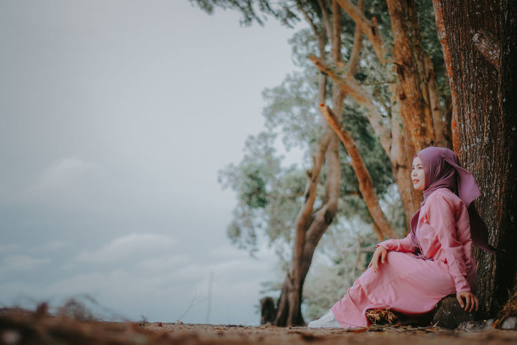 Girl sitting by tree against sky