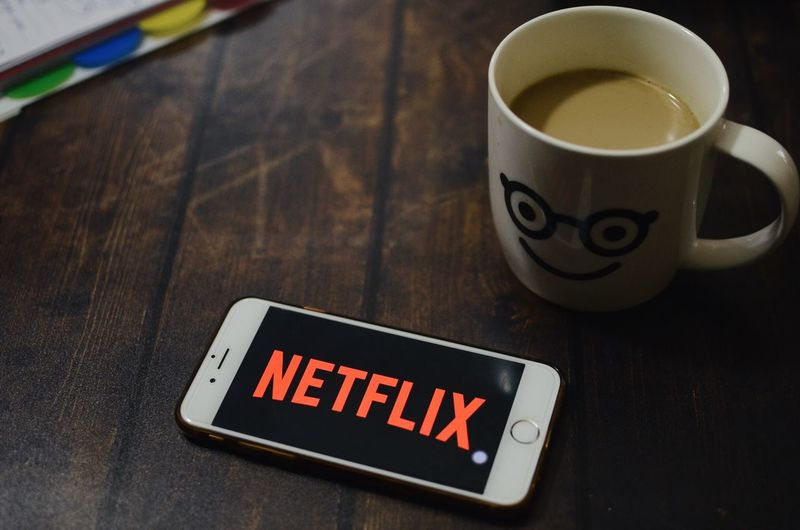 Netflix IPhone Text Western Script Communication Cup Indoors  Drink Mug Food And Drink Table No People Still Life High Angle View Close-up Coffee Cup Coffee Refreshment Sign Coffee - Drink Message Capital Letter