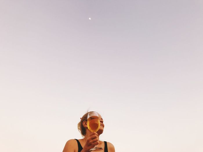 Woman holding drink against clear sky