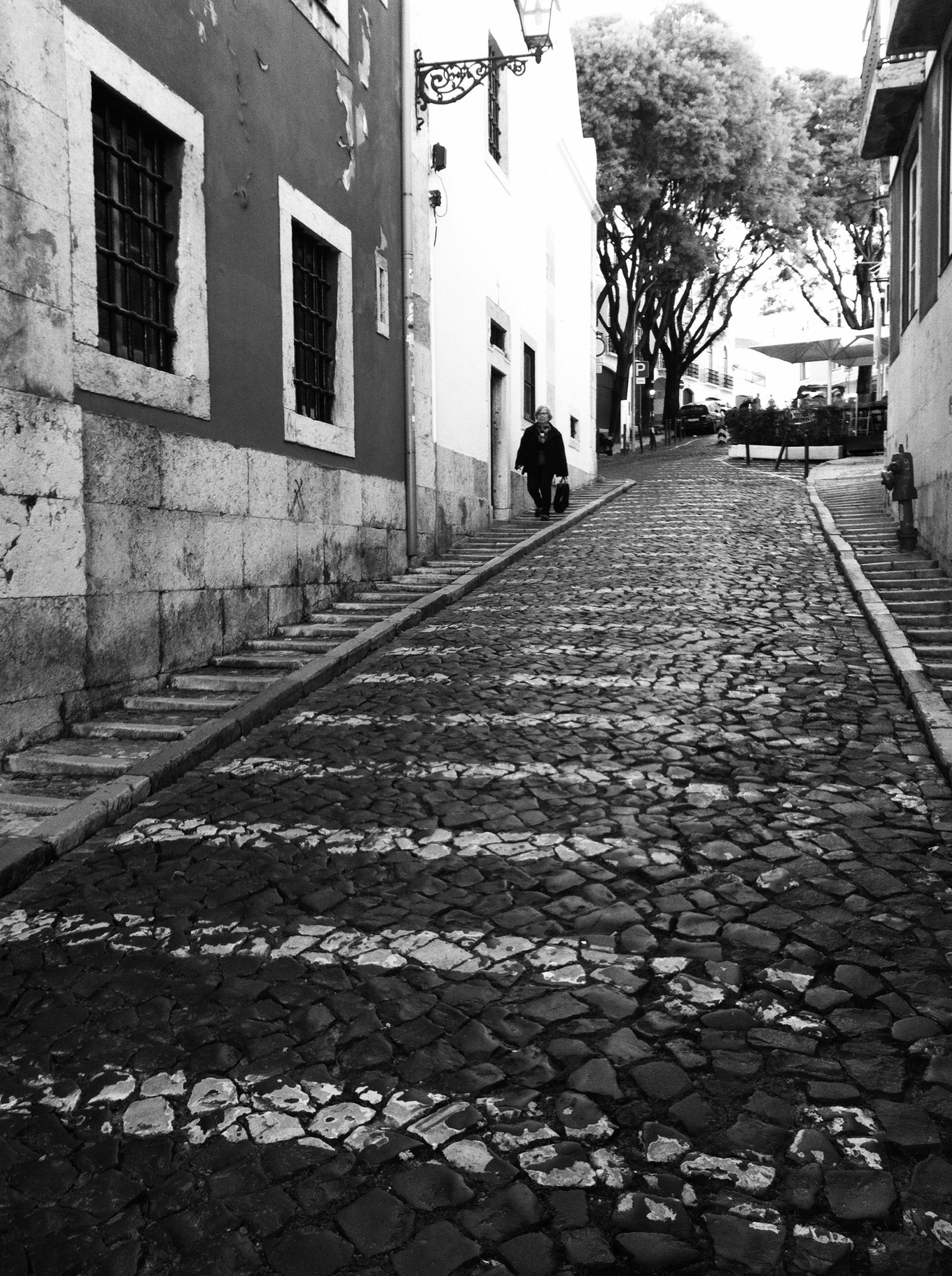 building exterior, architecture, built structure, the way forward, street, cobblestone, men, walking, city, transportation, lifestyles, diminishing perspective, day, residential structure, building, house, rear view, road