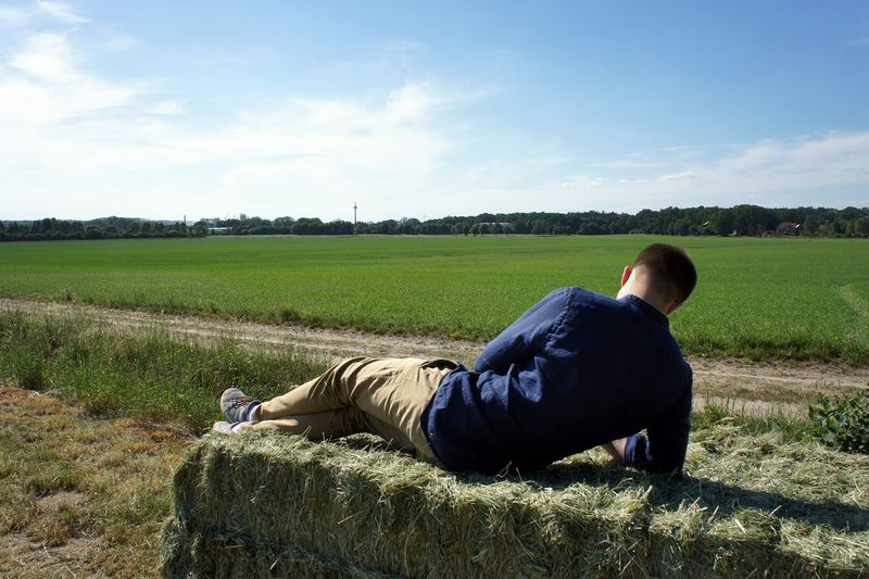 Casual Clothing Day Environment Field Full Length Grass Green Color Land Landscape Leisure Activity Lifestyles Lying Down Nature One Person Outdoors Plant Real People Rear View Relaxation Sky