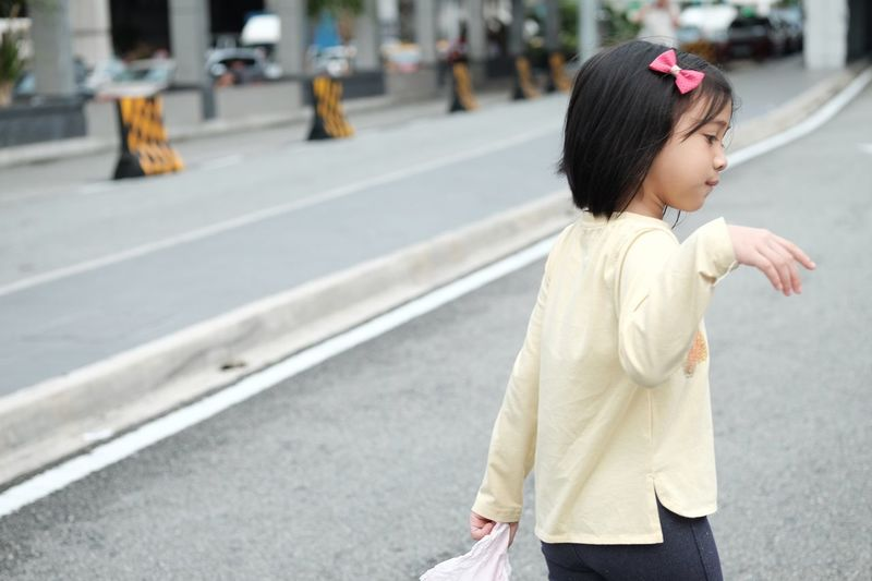 Side View Of Girl Walking On Road